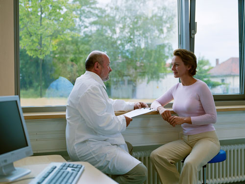 A patient talking with her dentist about reducing pain during treatments.