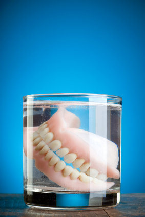 A pair of dentures floating in a glass jar.